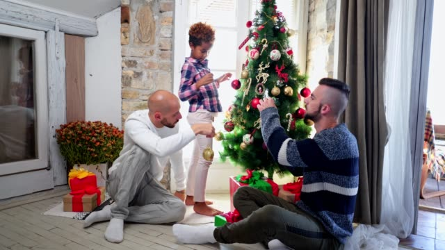 lovely adopted daughter decorating a tree with gay parents - decorating the christmas tree stock videos & royalty-free footage