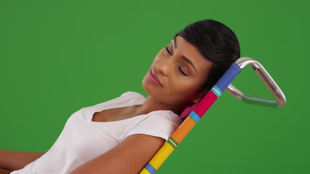 Lovely African American female in her 20s lounging on chair on green screen
