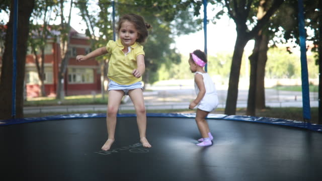 lovely and cute mixed race children jumping on a trampoline - family with two children stock videos & royalty-free footage