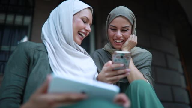 vídeos de stock, filmes e b-roll de lindas e pacíficas das mulheres muçulmanas olhando para mídias sociais - vestuário modesto
