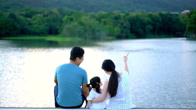 素敵なアジア家族自然湖ビューの背景と日没でリラックス