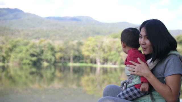 slo mo lovely asian mother and baby with nature lake - pointing stock videos & royalty-free footage