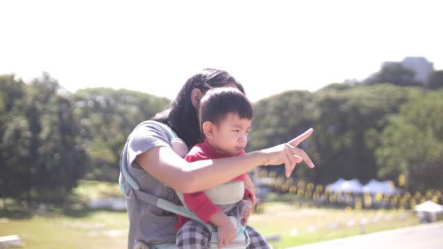 slo mo 素敵なアジアの母と自然湖と赤ちゃん - 指差す点の映像素材/bロール