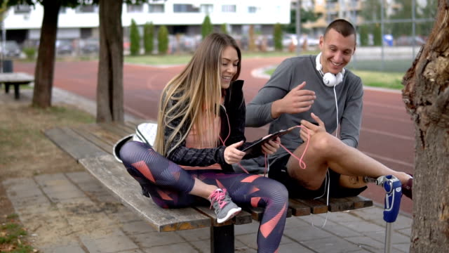 lovely athletic couple laughing while listening to music - amputee stock videos & royalty-free footage