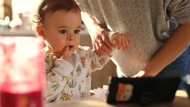 schöne baby junge beobachten cartoons auf handy und beißen seine finger - single mother stock-videos und b-roll-filmmaterial