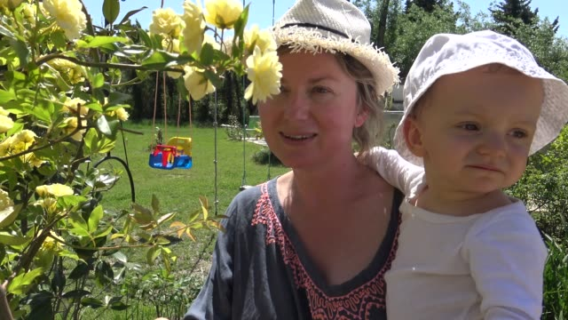 lovely baby girl walking with mother in beautiful garden - smelling stock videos & royalty-free footage