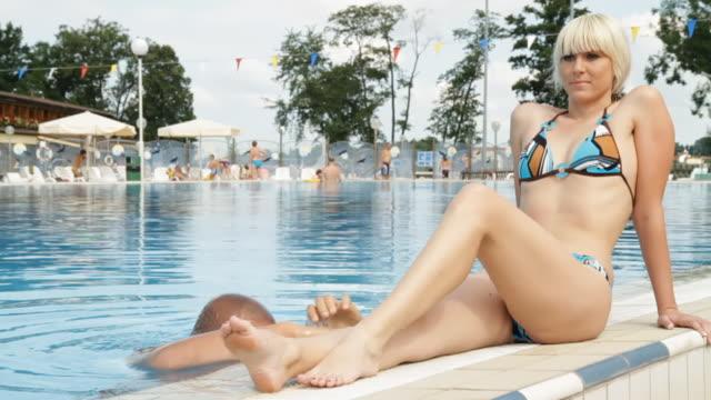 hd dolly: lovely couple at swimming pool - utebassäng bildbanksvideor och videomaterial från bakom kulisserna