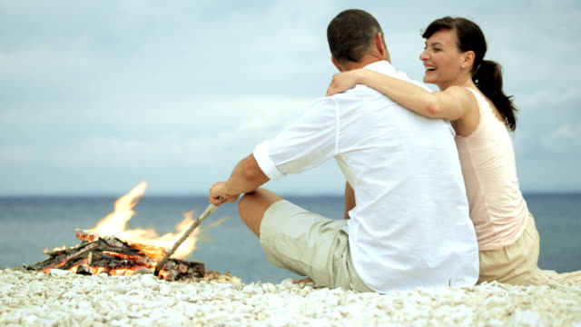 Lovely couple hugging and talking on the beach by fire