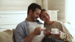 Lovely couple in love talking sitting on couch drinking tea
