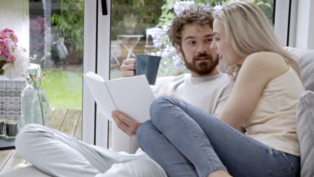 Lovely couple reading a book together relaxing on the couch