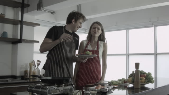 lovely couple with apron cooking in kitchen - employee engagement stock videos & royalty-free footage