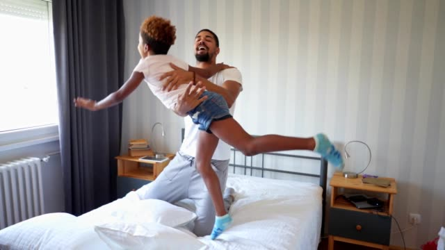 lovely daughter jumping in bed with father - bed furniture stock videos & royalty-free footage