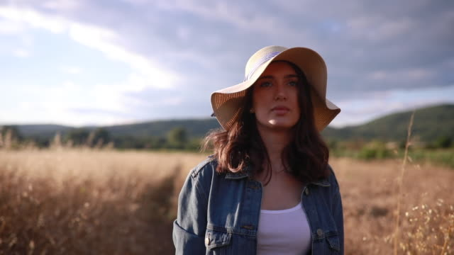 lovely day dreaming girl walking through a wheat field - denim jacket stock videos and b-roll footage