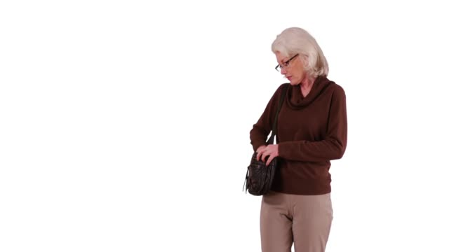 stockvideo's en b-roll-footage met lovely elder woman taking a walk pausing to answer text on white background - vaste stof