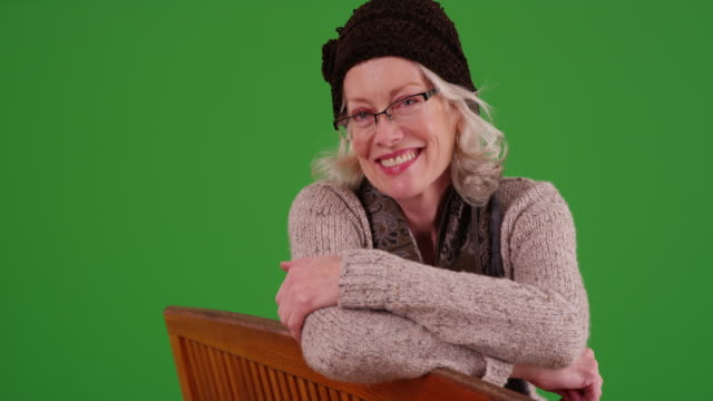 lovely elder woman with glasses sitting on bench smiling on greenscreen - sitting stock videos & royalty-free footage