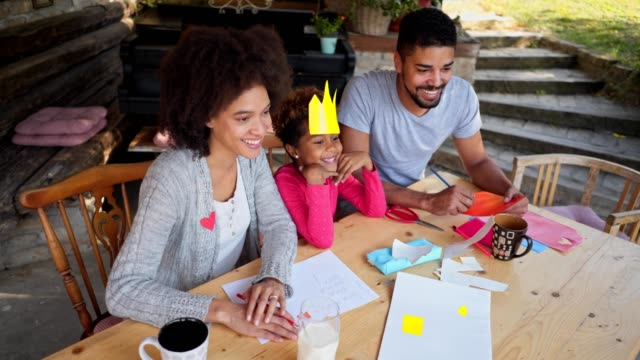 lovely family having fun while doing a art project for school - image stock videos & royalty-free footage