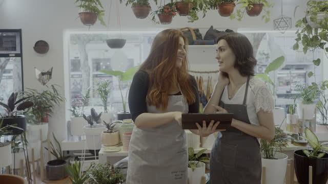 schöne weibliche mitarbeiter eines kleinen botanik-shops mit digitalem tablet - aussuchen stock-videos und b-roll-filmmaterial