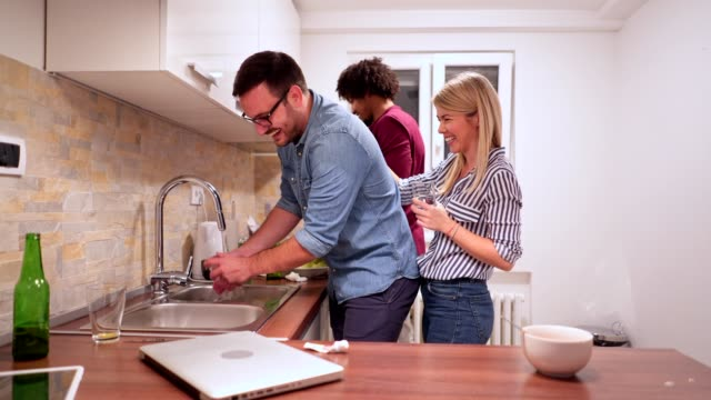 lovely friends washing dishes after dinner in a kitchen - after party stock videos & royalty-free footage
