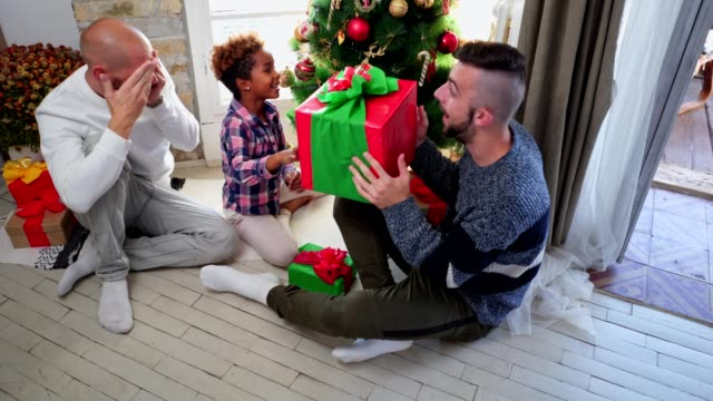 lovely gay parents having fun while decorating for christmas with their adopted daughter - decorating the christmas tree stock videos & royalty-free footage