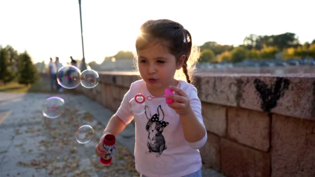 lovely girl blowing bubbles out of soap - soap sud video stock e b–roll