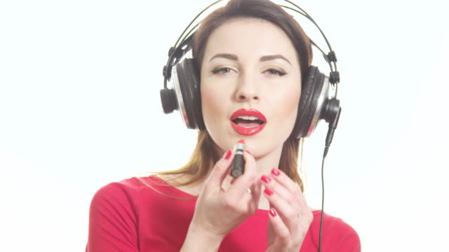 lovely girl in red listening to the music in big headphones and dancing having fun applying red lipstick isolated on white background close up shot - red lipstick stock videos & royalty-free footage
