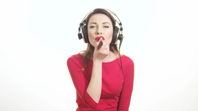 lovely girl in red listening to the music in big headphones and dancing having fun applying red lipstick isolated on white background medium shot - red lipstick stock videos & royalty-free footage