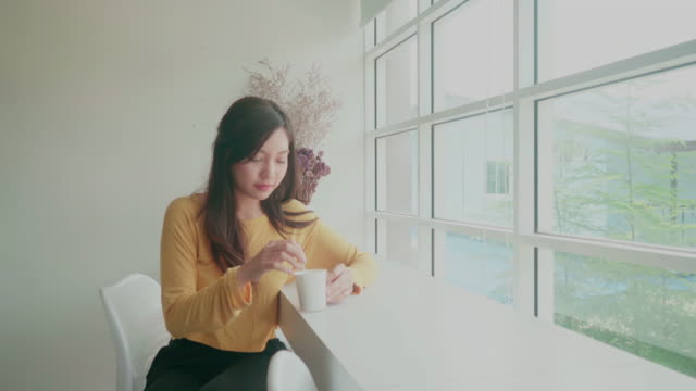 lovely girl sitting drink coffee at the window of a coffee cafe. - coffee drink stock videos & royalty-free footage
