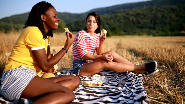 vidéos et rushes de jolies filles manger le gâteau en nature sur un pique-nique - picnic