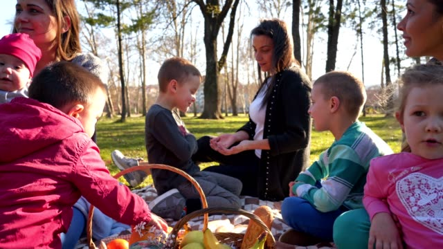 vidéos et rushes de beau groupe de parents et enfants ayant un pique-niquer à l'extérieur - panier pique nique