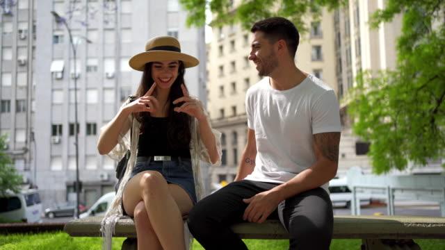 vidéos et rushes de beau couple de touristes hispaniques prenant une pause de l'aventure de ville - coup de foudre