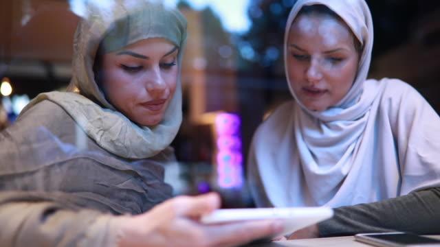vídeos de stock e filmes b-roll de lovely islamic students looking at a digital tablet at a cafe - emigração e imigração
