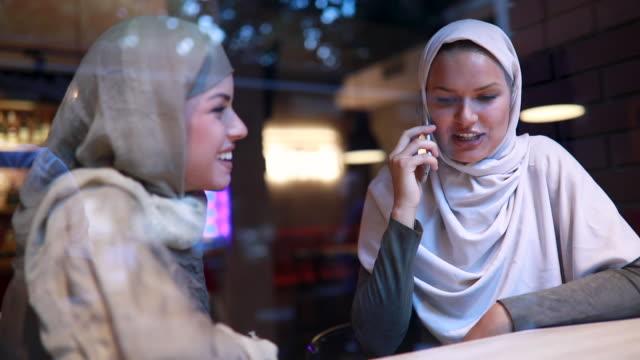 vídeos y material grabado en eventos de stock de mujeres islámicas hablando por un teléfono en un café - inmigrante