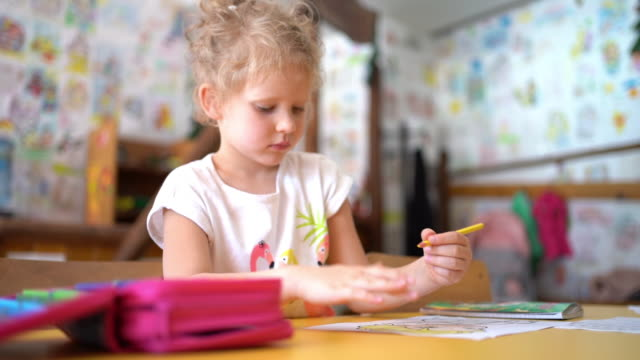 lovely little blond girl doing homework - quaderno video stock e b–roll
