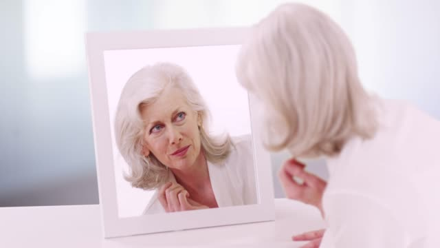 lovely mature woman checking her reflection inside bathroom fixing her hair - long beach california stock videos & royalty-free footage