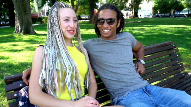 lovely multiracial couple sitting on the park bench and talking. - contrasts stock videos and b-roll footage