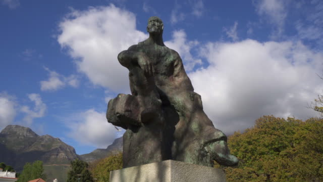 stockvideo's en b-roll-footage met a lovely pan of a bronze statue at the rhodes memorial under a blue sky with patchy clouds - cape town, south africa - memorial
