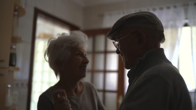 vídeos de stock, filmes e b-roll de adorável casal sênior dançando em casa - carinhoso