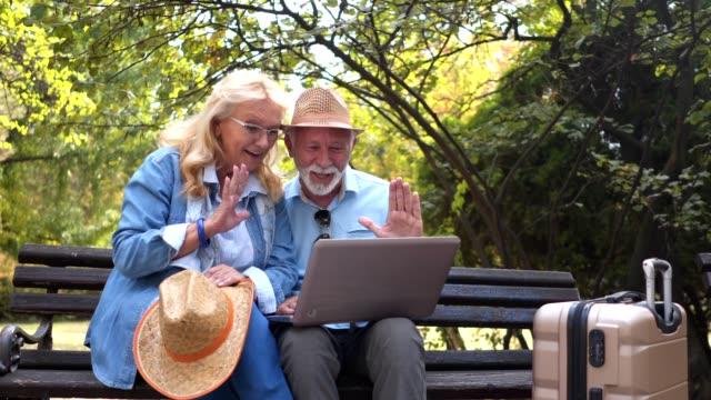 vidéos et rushes de beau couple de personnes âgées ayant un grand temps de parler sur un appel vidéo au cours de voyages - banc