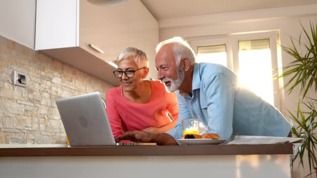 lovely senior couple in a sunny kitchen enjoying a beautiful morning - the ageing process stock videos & royalty-free footage
