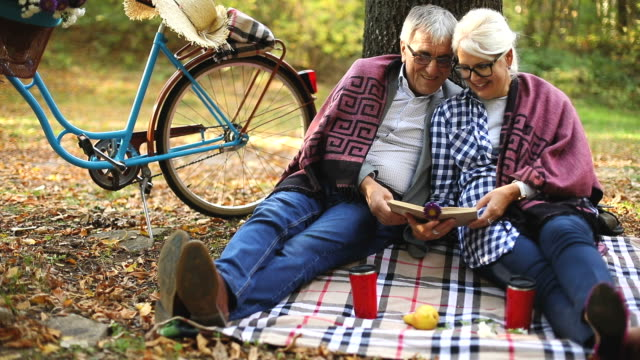 lovely senior couple resting at park, reading a book - hugging tree stock videos & royalty-free footage