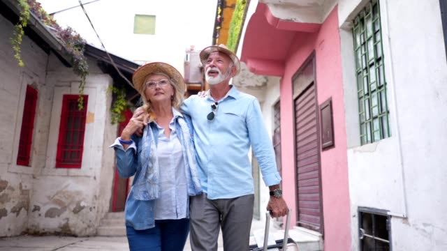 lovely senior couple walking through a city street and looking around - tourist stock videos & royalty-free footage
