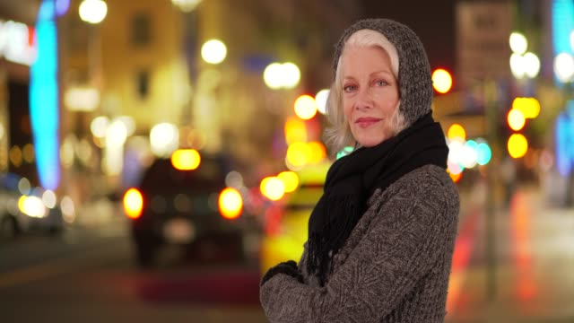 lovely senior woman smiling at camera on busy downtown street with bokeh lights - pullover stock videos & royalty-free footage