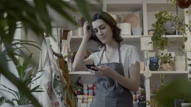 素敵な店長は、小さな植物園やギフトショップで休憩中にスマートフォンを使用しています - ギフトショップ点の映像素材/bロール
