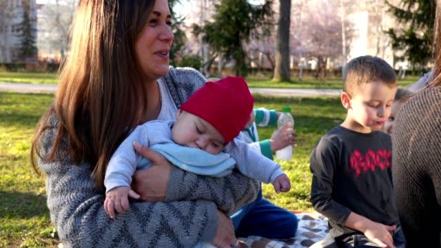 vidéos et rushes de beau bébé endormi a tenu ma sa mère à l'extérieur sur un pique-niquer - picnic