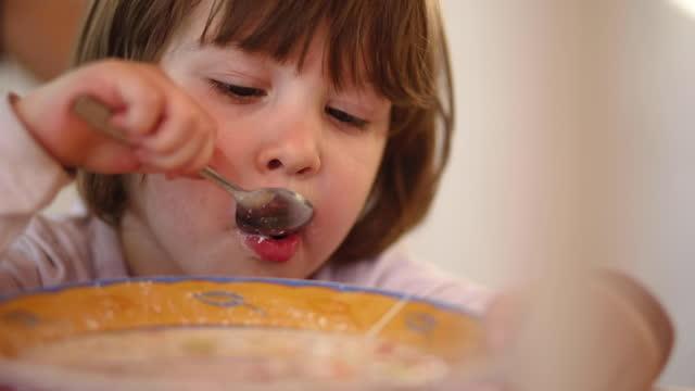 自家製スープを楽しむ素敵な笑顔の幼児の女の子 - スープ点の映像素材/bロール