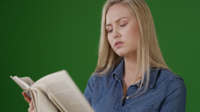 Lovely young female student reading on green screen