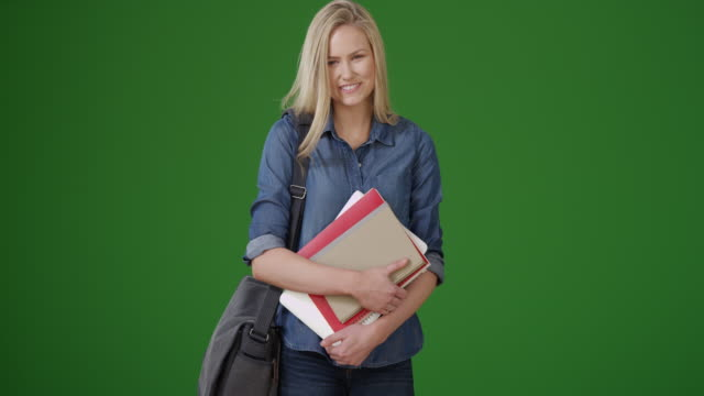 Lovely young female student standing on green screen