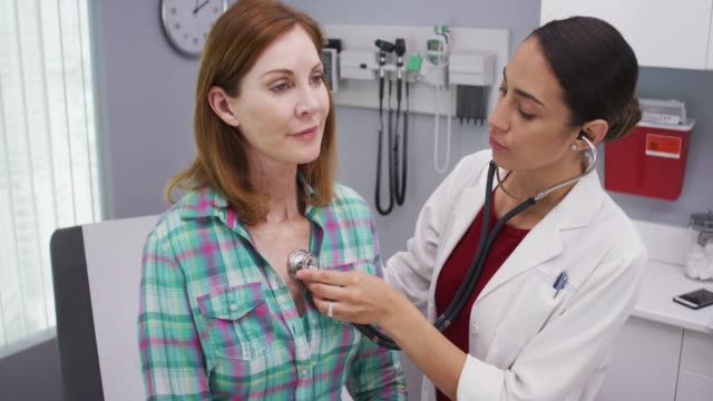 lovely young latina doctor using stethoscope to examine senior patients vitals - medical instrument stock videos and b-roll footage