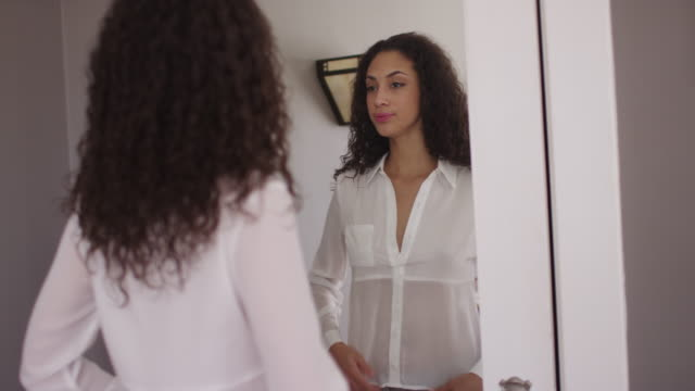 stockvideo's en b-roll-footage met lovely young latino woman dressing in front of mirror - slank