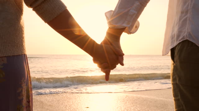 lovers holding hands at the beach. - holding hands stock videos & royalty-free footage